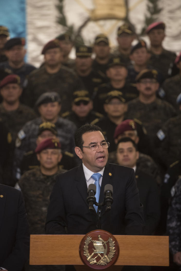 Guatemalan President Jimmy Morales speaks to the nation in a televised address, surrounded by military officers, in Guatemala City, Friday, Aug. 31, 2018. Morales said he is not renewing the mandate of a U.N.-sponsored commission that has pressed a number of high-profile corruption probes in the country, including against him. (AP Photo/Oliver de Roos)