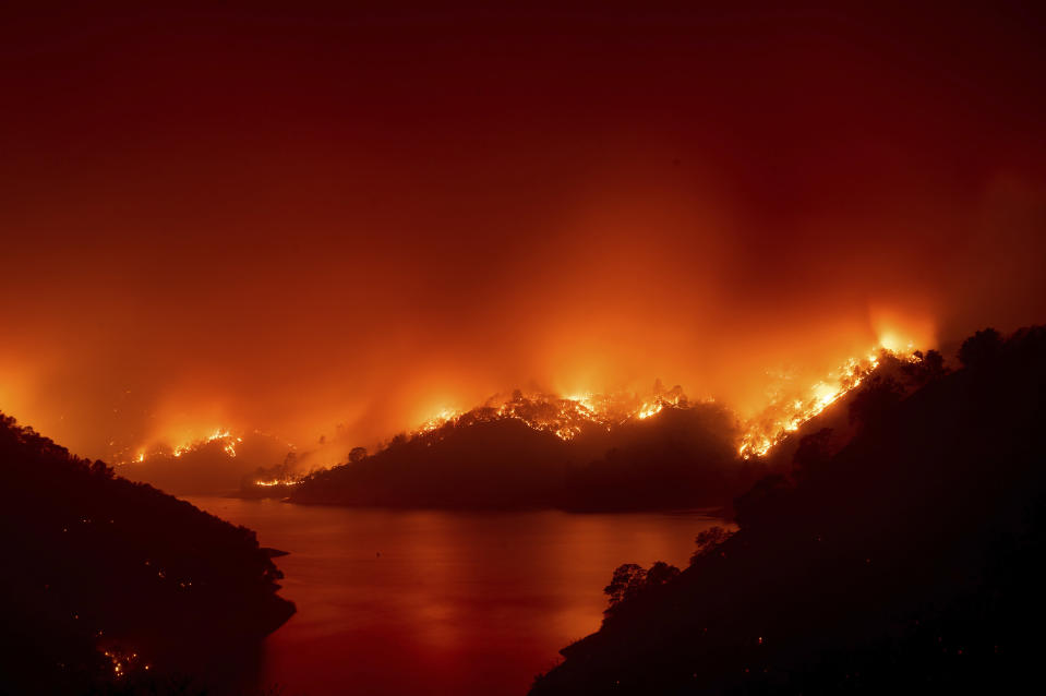 Flames from the LNU Lightning Complex fires burn around Lake Berryessa in unincorporated Napa County, Calif., on Wednesday, Aug. 19, 2020. Fire crews across the region scrambled to contain dozens of wildfires sparked by lightning strikes. (AP Photo/Noah Berger)