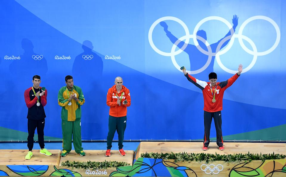 RIO DE JANEIRO, BRAZIL - AUGUST 12: (R-L) Joint silver medalists, Michael Phelps of United States, Chad Guy Bertrand le Clos of South Africa, Laszlo Cseh of Hungary and gold medalist Joseph Schooling of Singapore celebrate on the podium during the medals ceremony in the Men's 100m Butterfly Final on Day 7 of the Rio 2016 Olympic Games at the Olympic Aquatics Stadium on August 12, 2016 in Rio de Janeiro, Brazil.  (Photo by Richard Heathcote/Getty Images)