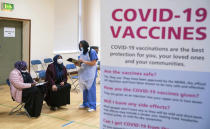 People attend a pop-up Covid-19 vaccination centre, at the East London Mosque in Whitechapel, London, Saturday Feb. 6, 2021. Britain's vaccination program is pushing to offer a vaccination to aged, vulnerable and care workers by mid-February. (Dominic Lipinski/PA via AP)