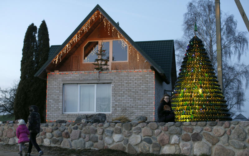 Goda Valukonyte poses by the bottle Christmas tree in Agariniu village, Lazdijai district, some 176 kilometers (110 miles) from Vilnius, Lithuania, Saturday, Dec. 28, 2013. Lithuanian policeman Dalius Valukonis says he spent three years and hundreds of hours of his free time to create the tree using bottles he got from local restaurants, bars, family and friends. (AP Photo/Mindaugas Kulbis)