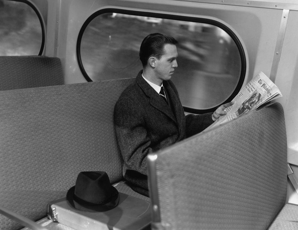 <p>Before podcasts and social media scrolling were available to relieve us from boredom, commuters often passed the time by reading up on the news. Here, a businessman is flipping through a newspaper during his daily commute on the bus. </p>