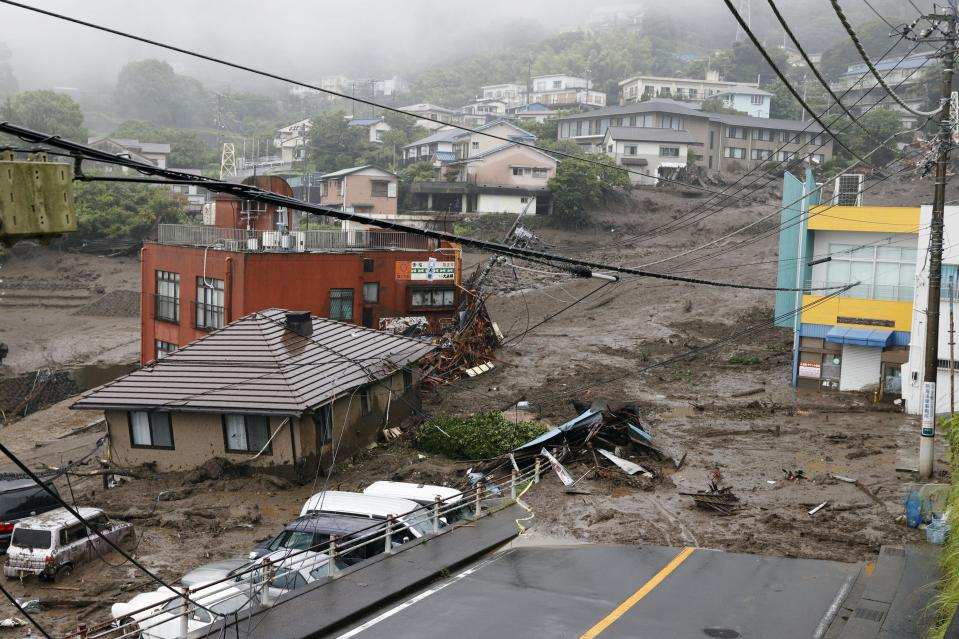 This photo shows buildings damaged by a mudslide at the Izusan district in Atami, west of Tokyo, Saturday, July 3, 2021, following heavy rains in the area. The mudslide carrying a deluge of black water and debris crashed into rows of houses in the town following heavy rains on Saturday, leaving multiple people missing, officials said. (Kyodo News via AP)