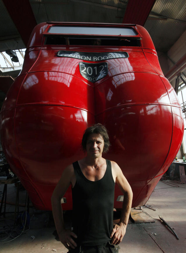 Czech artist David Cerny poses next to a London bus that he has transformed into a robotic sculpture in Prague July 2, 2012. The bus, which Cerny hopes could become an unofficial mascot of the London 2012 Olympic Games, does push-ups with the help of an engine powering a pair of robotic arms, and the motion is accompanied by a recording of sounds evoking tough physical effort. It will be parked outside the Czech Olympic headquarters in London for the duration of the Games. Picture taken July 2, 2012. REUTERS/Petr Josek (CZECH REPUBLIC - Tags: SOCIETY SPORT OLYMPICS TRANSPORT)