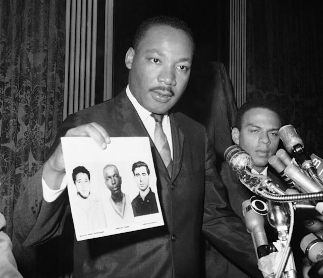<p>Civil rights leader Dr. Martin Luther King displays pictures of three civil rights workers at a news conference in New York on Dec. 4, 1964. The workers were slain in Mississippi last summer. Dr. King commended the FBI for its arrests in Mississippi on Dec. 4, 1964 in connection with the slayings. (Photo: JL/AP) </p>