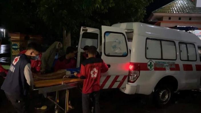 An injured person is being moved into an ambulance following an earthquake in Mamuju
