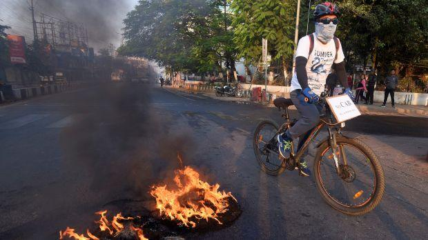 A cyclist passes burning tyres set ablaze by protesters during the strike called by AACSU to protest against the bill in Guwahati