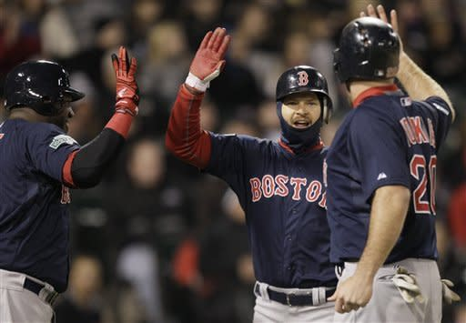 Boston Red Sox's Cody Ross, center, celebrates with Kevin Youkilis, right, and David Ortiz after scoring on a three-run double by Darnell McDonald during the sixth inning of a baseball game against the Chicago White Sox in Chicago, Friday, April 27, 2012. (AP Photo/Nam Y. Huh)