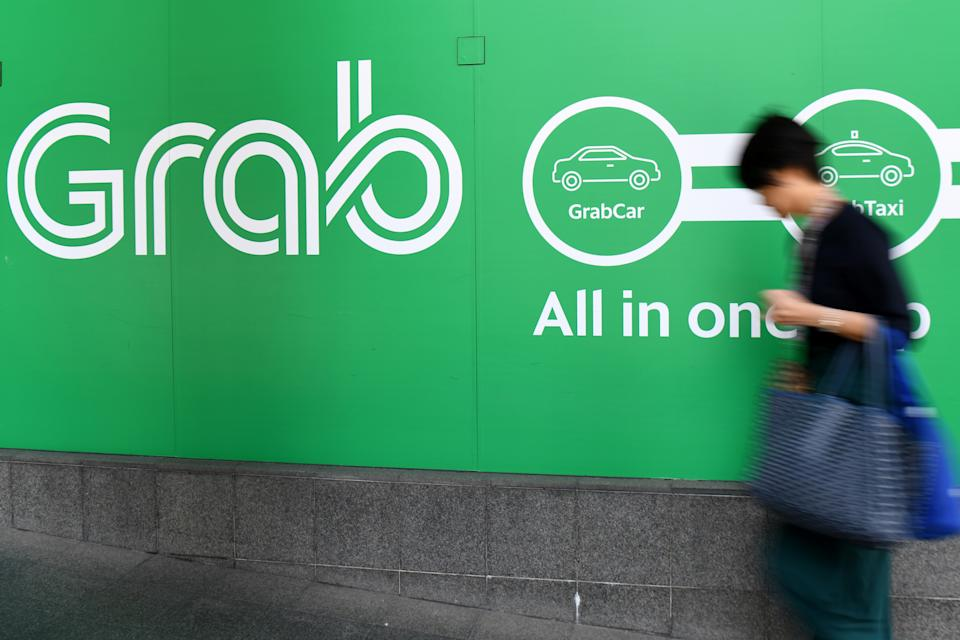 A woman walks past the Grab transport office in Singapore on September 24, 2018. - Singapore on September 24, fined ride-hailing firms Grab and Uber $9.5 million for breaking competition rules when they merged, saying the deal had increased fares and thrown up roadblocks for competitors. (Photo by ROSLAN RAHMAN / AFP)        (Photo credit should read ROSLAN RAHMAN/AFP via Getty Images)
