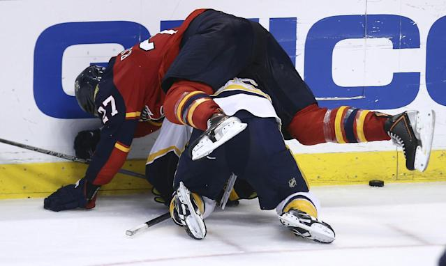 Florida Panthers' Nick Bjudstad (27) lands atop of Nashville Predators' Colin Wilson (33) as they fight for the puck during the third period of a NHL hockey game in Sunrise, Fla., Saturday, Jan. 4, 2014. The Panthers won 5-4 in an overtime shootout. (AP Photo/J Pat Carter)