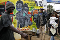 """FILE - In this July 8, 2020, file photo, people walk past an informational mural warning people about the dangers of the new coronavirus and how to prevent transmission, with words in Swahili reading """"We are the Cure"""", painted by youth artists from the Uweza Foundation, in the Kibera slum, or informal settlement, of Nairobi, Kenya. A dangerous stigma has sprung up around the coronavirus in Africa — fueled, in part, by severe quarantine rules in some countries as well as insufficient information about the virus. (AP Photo/Brian Inganga, File)"""