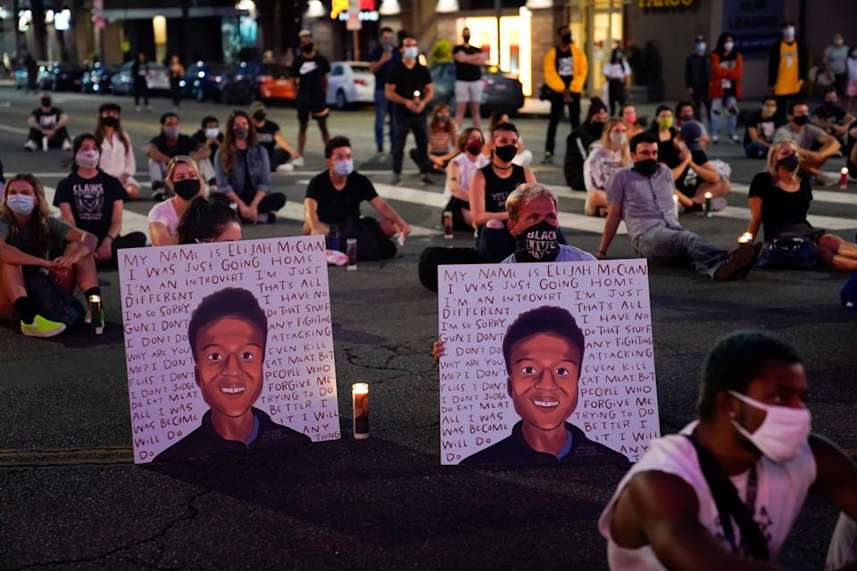 In this Aug. 24, 2020, file photo, two people hold posters showing images depicting Elijah McClain during a candlelight vigil for McClain outside the Laugh Factory in Los Angeles.