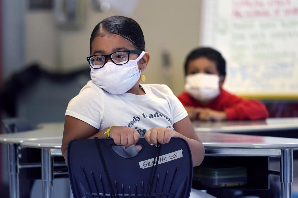 A a summer school student wears a protective mask while listening to instruction, at the E.N. White School in Holyoke, Mass., on Wednesday, Aug. 4, 2021. Schools across the U.S. are about to start a new year amid a flood of federal money larger than they've ever seen before, an infusion of pandemic relief aid that is four times the amount the U.S. Department of Education sends to K-12 schools in a typical year. (AP Photo/Charles Krupa)