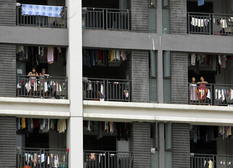 FILE-In this Wednesday, May 26, 2010, file photo, employees stand on the balconies of a residential house at the Foxconn complex in Shenzhen, China. Foxconn, the company that makes Apple's iPhones suspended production at a factory in China on Monday, Sept. 24, 2012, after a brawl by as many as 2,000 employees at a dormitory injured 40 people. The fight, the cause of which was under investigation, erupted Sunday night at a privately managed dormitory near a Foxconn Technology Group factory in the northern city of Taiyuan, the company and Chinese police said. (AP Photo/Kin Cheung, File)