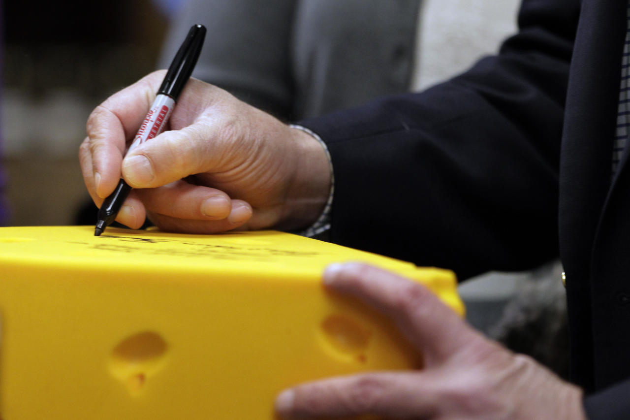 Republican presidential candidate, former Pennsylvania Sen. Rick Santorum signs his autograph on a cheese head hat at Simon's Specialty Cheese in Appleton, Wis., Monday, April 2, 2012. (AP Photo/Jae C. Hong)