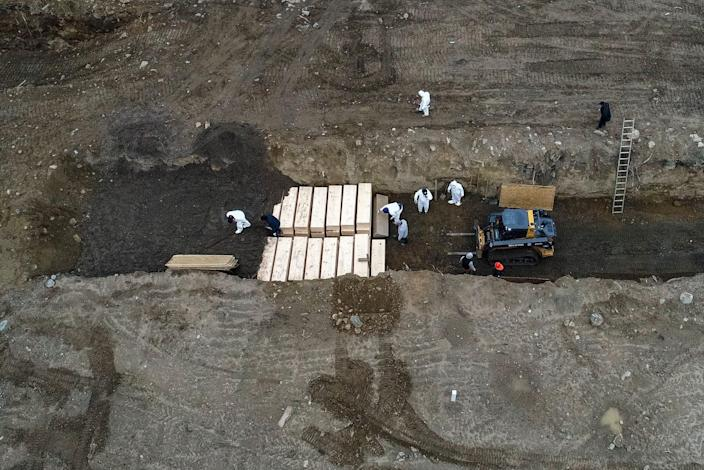 Workers wearing personal protective equipment bury bodies in a trench on Hart Island in the Bronx borough of New York. A disproportionate number of New York's coronavirus deaths have hit the city's Latino community.