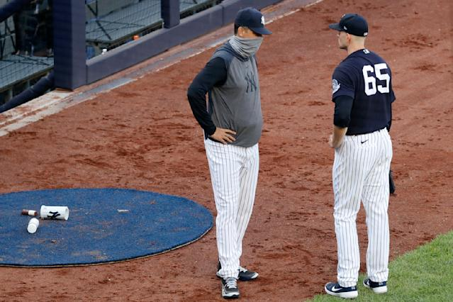 New York Yankees manager Aaron Boone, left, talks to pitcher James Paxton between innings during an intrasquad baseball game in New York. Paxton allowed two home runs in the first inning and struck a batter with a pitch. (AP Photo/Kathy Willens)