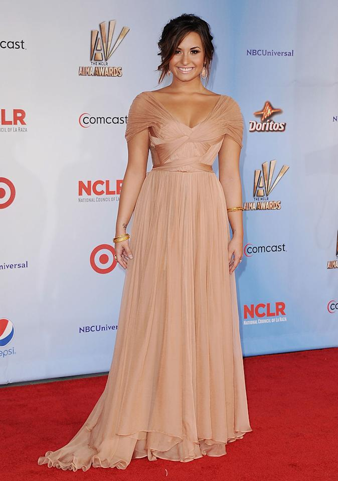 "Following in Alba's footsteps was former Disney darling Demi Lovato, who looked better than ever in a nude Maria Lucia Hohan gown. Gold bangles, a loose updo, and fresh makeup completed her flawless ensemble. Jon Kopaloff/<a href=""http://www.filmmagic.com/"" target=""new"">FilmMagic.com</a> - September 10, 2011"
