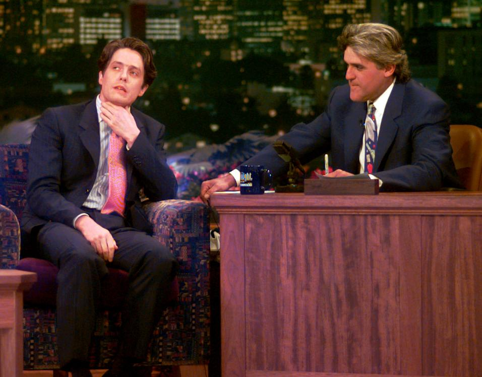 "British actor Hugh Grant,left, reacts to a question about his arrest for lewd conduct from host Jay Leno during the early moments on ""The Tonight Show with Jay Leno"" , Monday, July 10, 1995 in Burbank, Calif. It was Grant's first publicity appearance since his arrest involving a prostitute. (AP Photo/Eric Draper)"
