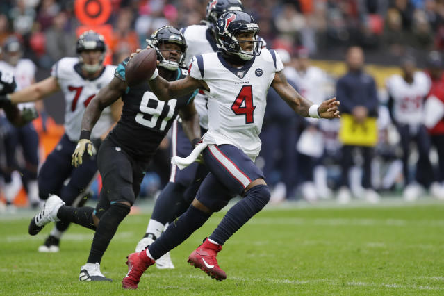 Houston Texans quarterback Deshaun Watson (4) runs out of the pocket under pressure by Jacksonville Jaguars defensive end Yannick Ngakoue (91) during the first half of an NFL football game at Wembley Stadium, Sunday, Nov. 3, 2019, in London. (AP Photo/Kirsty Wigglesworth)