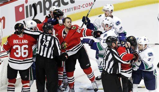 Chicago Blackhawks' Viktor Stalberg (25) grabs Vancouver Canucks' Alexander Edler (23) as players from both teams fight during the second period of an NHL hockey game in Chicago, Wednesday, March 21, 2012. (AP Photo/Charles Rex Arbogast)