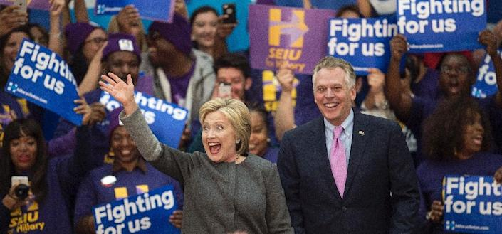 Democratic presidential hopeful Hillary Clinton (L) waves to the crowd beside Virginia Governor Terry McAuliffe during a campaign rally on February 29, 2016 at George Mason University in Fairfax, Virginia (AFP Photo/Paul J. Richards)