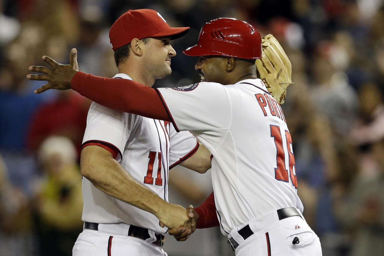 Washington Nationals third base coach Bo Porter (16) embraces third baseman Ryan Zimmerman (11) after their 4-1 win over the Los Angeles Dodgers, earning them a playoff spot, during their baseball game at Nationals Park, in Washington, Thursday, Sept. 20, 2012. (AP Photo/Jacquelyn Martin)