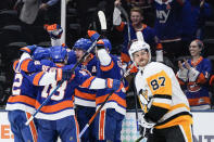 New York Islanders' Brock Nelson celebrates with teammates after scoring a goal as Pittsburgh Penguins' Sidney Crosby (87) skates past them during the second period of Game 6 of an NHL hockey Stanley Cup first-round playoff series, Wednesday, May 26, 2021, in Uniondale, N.Y. (AP Photo/Frank Franklin II)