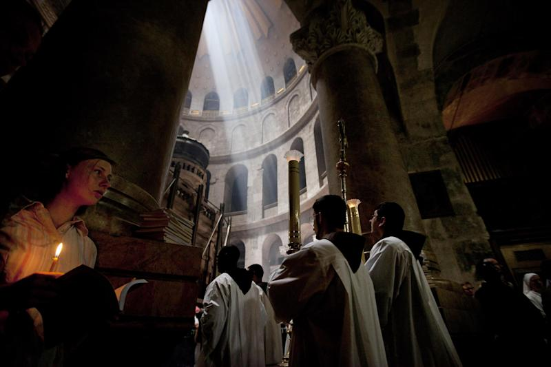 A Christian woman holds a candle inside the Church of the Holy Sepulchre, traditionally believed to be the burial site of Jesus Christ, in Jerusalem's Old City, Thursday, May 30, 2013. (AP Photo/Sebastian Scheiner)