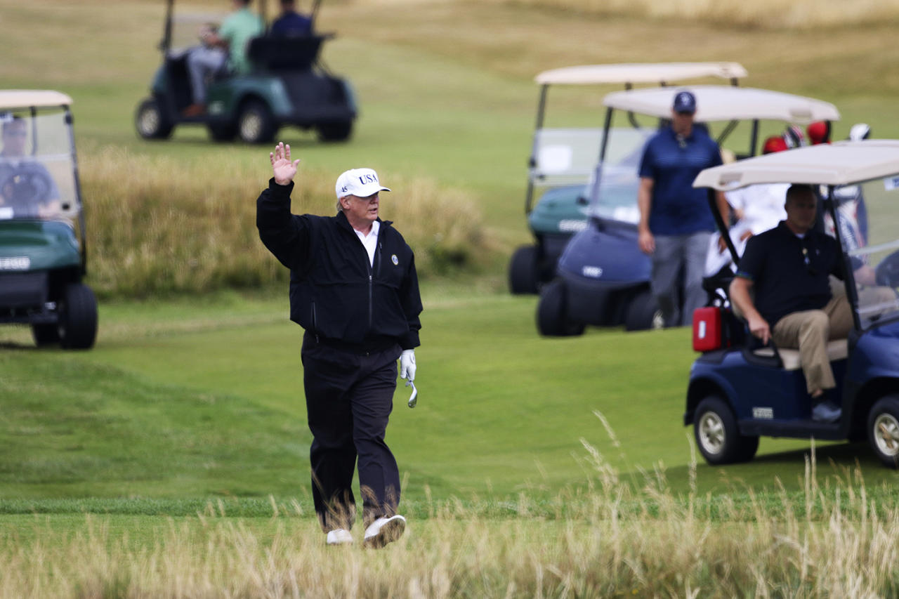 <p>President Donald Trump waves to protesters while playing golf at Turnberry golf club, in Turnberry, Scotland, Saturday, July 14, 2018. A dozen demonstrators have staged a protest picnic on the beach in front of the Trump Turnberry golf resort in Scotland where President Donald Trump is spending the weekend with the first lady. (Photo: Peter Morrison/AP) </p>