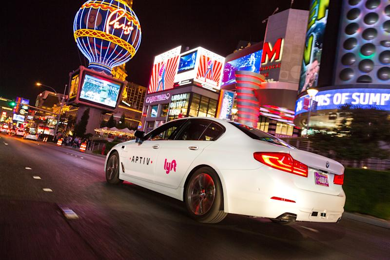An white BMW driving in Las Vegas with Lyft and Aptiv branding.