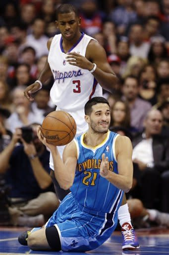 New Orleans Hornets point guard Greivis Vasquez (21) passes in front of Los Angeles Clippers point guard Chris Paul (3) during the first half of an NBA basketball game in Los Angeles, Monday, Nov. 26, 2012. (AP Photo/Chris Carlson)