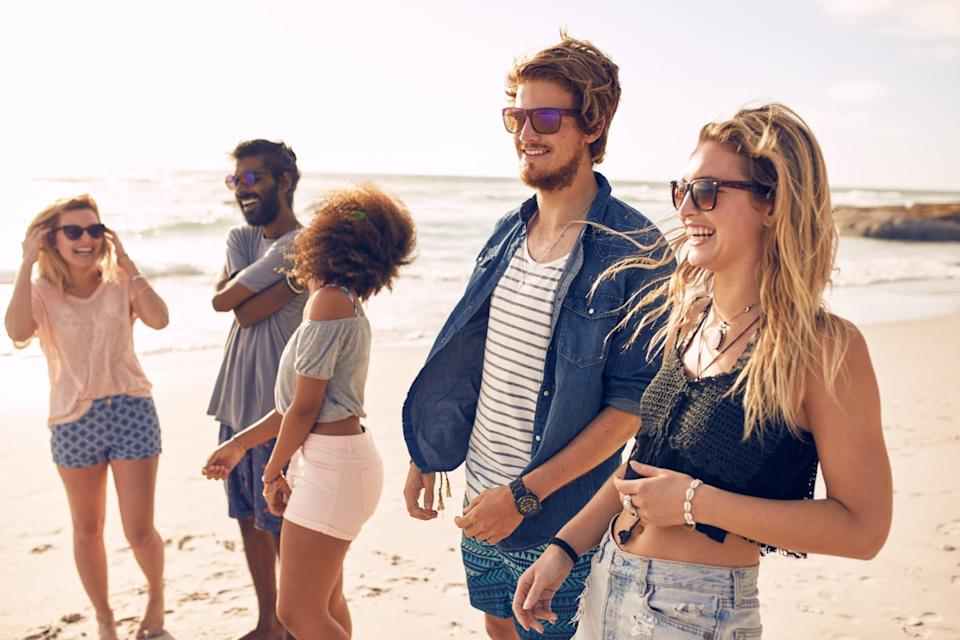 Group of friends walking along a beach at summertime