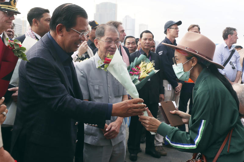 FILE - In this Feb. 14, 2020, file photo, Cambodia's Prime Minister Hun Sen, left, gives a bouquet of flowers to a passenger who disembarked from the MS Westerdam at the port of Sihanoukville, Cambodia. The feel-good story of how Cambodia allowed the cruise ship to dock after it was turned away elsewhere in Asia for fear of spreading the deadly virus that began in China has taken a dark turn after a passenger released from the ship tested positive for the virus. (AP Photo/Heng Sinith, File)