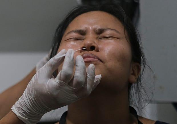 A health worker takes a nasal swab sample from a woman. Nova Scotia reported 34 new cases of COVID-19 on Friday. (Yirmiyan Arthur/The Associated Press - image credit)