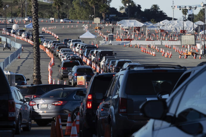 Los Angeles residents wait in line in their cars to receive a covid-19 vaccine at Dodger Stadium, Tuesday, Jan. 26, 2021, in Los Angeles. California is revamping its vaccine delivery system to give the state more control over who gets the shots following intense criticism of a slow and scattered rollout by counties. (AP Photo/Richard Vogel)