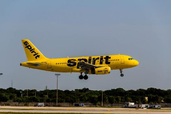 Yellow airplane with Spirit logo just about to land.