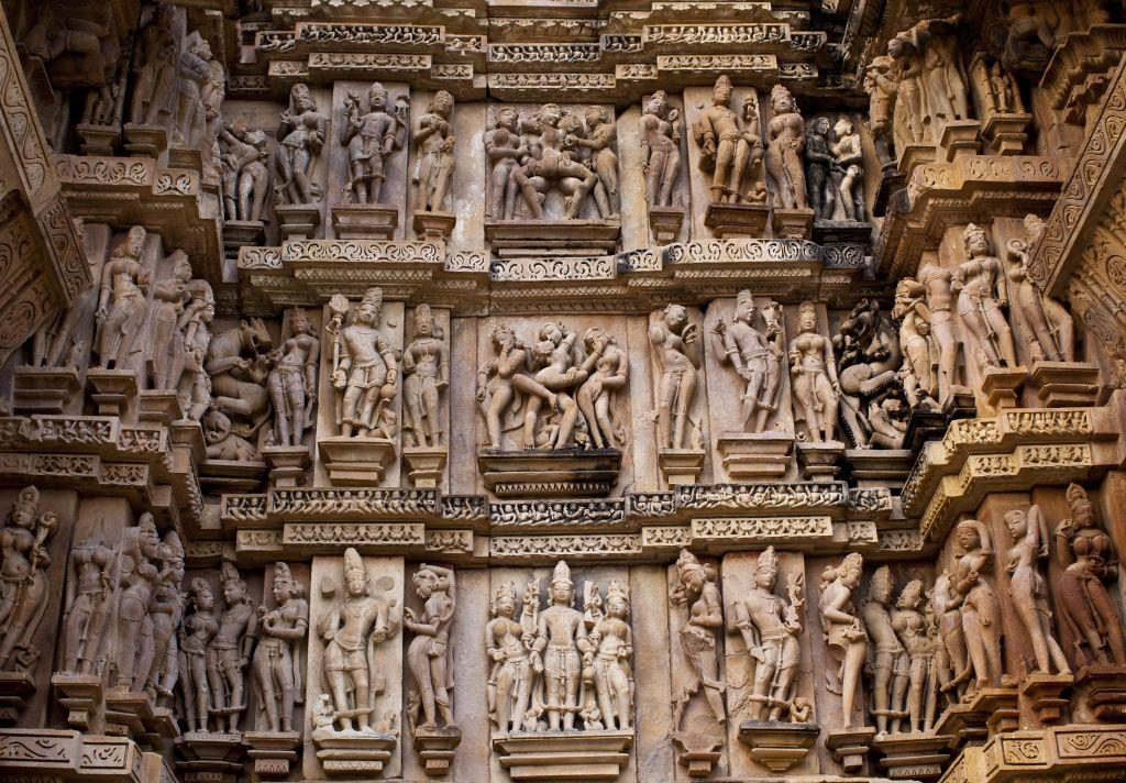 Reliefs and friezes show erotic figures on the temple walls in Khajuraho.