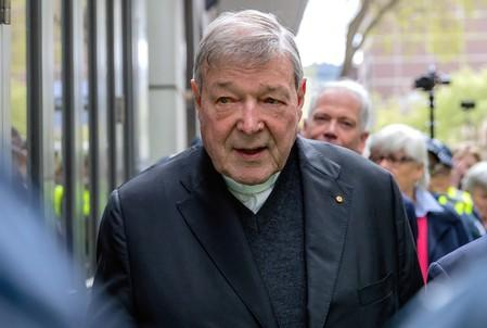 FILE PHOTO - Vatican Treasurer Cardinal George Pell is surrounded by Australian police as he leaves the Melbourne Magistrates Court in Australia