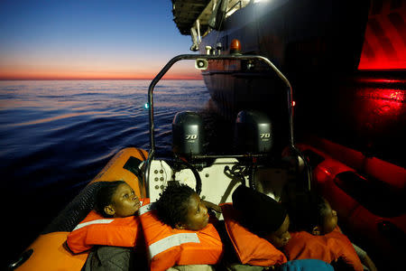 Migrants rescued from a rubber dinghy are brought to the Malta-based NGO Migrant Offshore Aid Station (MOAS) ship Phoenix at dawn in the central Mediterranean