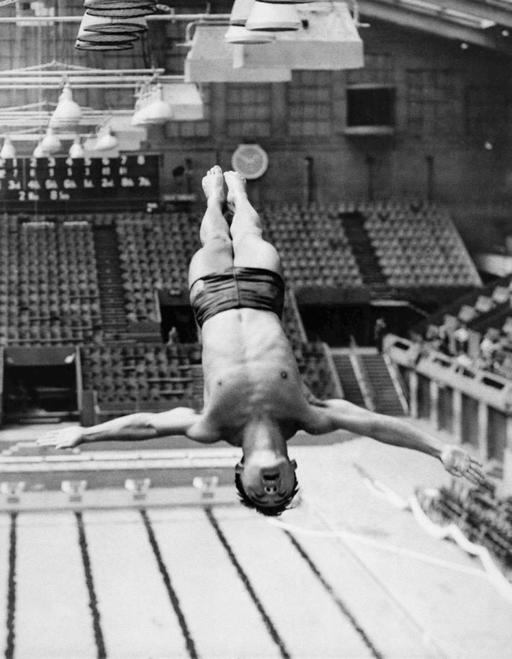 "FILE - This July 27, 1948 file photo shows Sammy Lee, member of the United States Olympic Diving Team, diving from the top of the diving tower during training at the Empire Pool in Wembley, London, England. Lee remembers the London 1948 Olympics vividly: the food rationing, the bombed-out buildings, the rubble. London was hosting the Olympics amid severe austerity conditions in the aftermath of World War II. The 2012 Olympics will showcase a much different London and a much different event from the 1948 ""Austerity Games"" held on a shoestring budget: This will be a $16 billion extravaganza featuring multimillionaire professionals, shiny new purpose-built venues and a revitalized East End. Britain's biggest peacetime project also comes with a massive security operation. (AP Photo/File)"