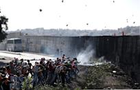 Palestinian demonstrators hurls rocks towards Israeli borderguards next to the controvertial wall separating the West Bank city of Abu Dis from east Jerusalem on November 2, 2015 (AFP Photo/Ahmad Gharabli)