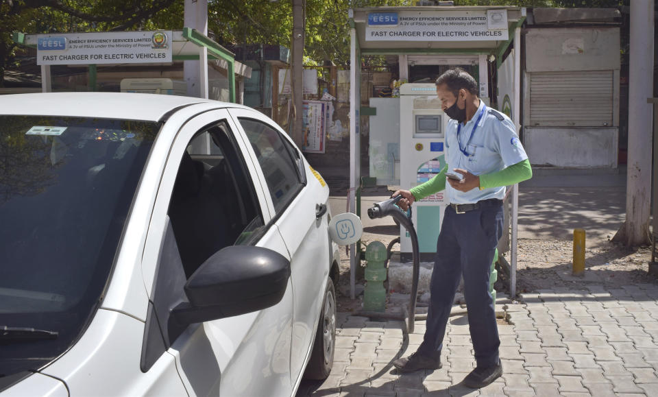 A driver of an electric car charges his vehicle at public charging station in New Delhi, India, Thursday, April 1, 2021. India has ambitions to expand use of electric vehicles to wean itself from polluting fossil fuels, but EVs are still a rarity on its congested highways. A lack of charging stations and poor quality batteries are discouraging drivers from switching over. (AP Photo/Neha Mehrotra)