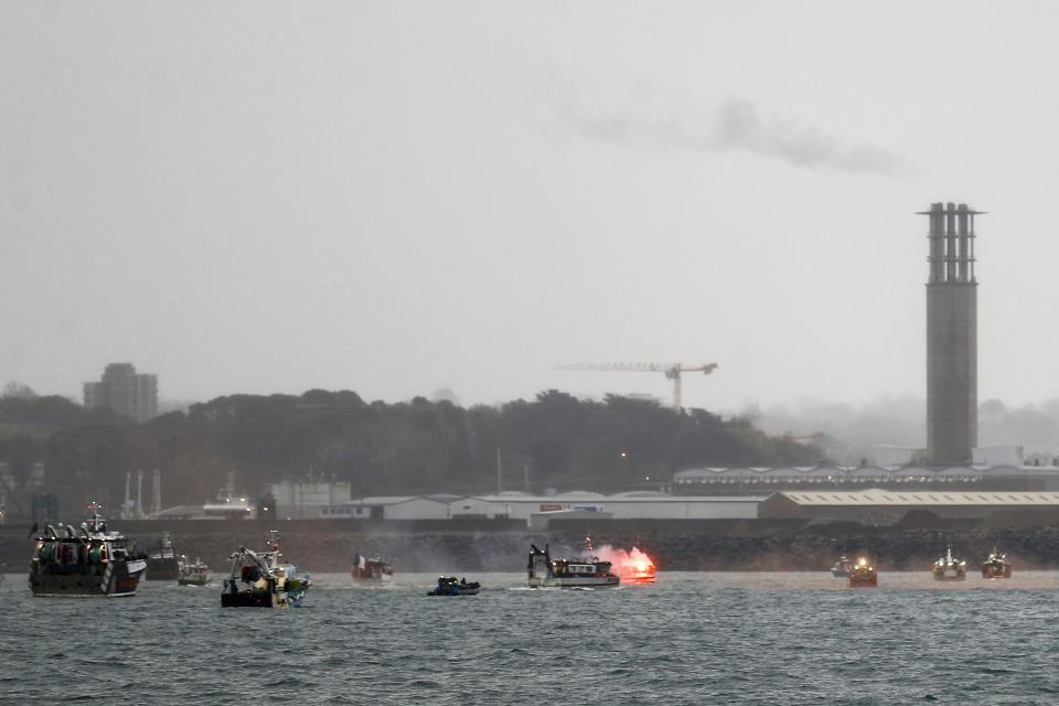 A flare is lit as French fishing boats protest in front of the port of Saint Helier off the British island of Jersey to draw attention to what they see as unfair restrictions on their ability to fish in UK waters after Brexit, on May 6, 2021. - Around 50 French fishing boats gathered to protest at the main port of the UK island of Jersey on May 6, 2021, amid fresh tensions between France and Britain over fishing. The boats massed in front of the port of Saint Helier to draw attention to what they see as unfair restrictions on their ability to fish in UK waters after Brexit, an AFP photographer at the scene said. (Photo by Sameer Al-DOUMY / AFP) (Photo by SAMEER AL-DOUMY/AFP via Getty Images)