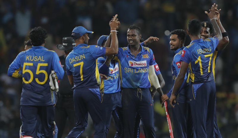 Sri Lankan team members celebrate their victory over West Indies' by six runs in the third one day international cricket match between Sri Lanka and West Indies in Pallekele, Sri Lanka, Sunday, March 1, 2020. (AP Photo/Eranga Jayawardena)