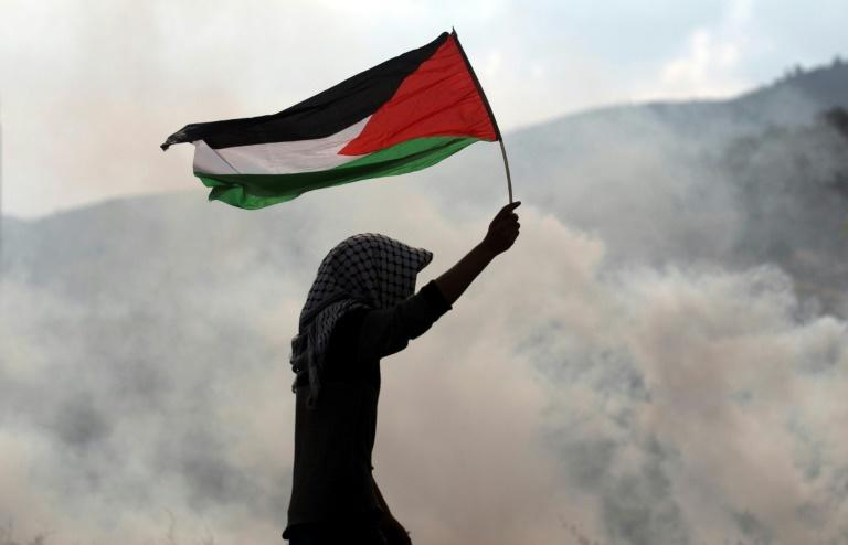 A protester waves a Palestinian flag amid tear gas during clashes with Israeli security forces near the Huwara checkpoint south of Nablus in the occupied West Bank on December 15, 2017