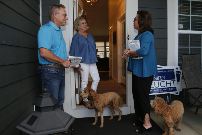Jennifer Feucht, right, candidate for Olentangy Local Board of Education, delivers campaign flyers and yard signs to Brad, left, and Tina Krider Thursday, Oct. 7, 2021, in Westerville, Ohio. Across Ohio and the nation, parental protests over social issues like mask mandates, gender-neutral bathrooms, teachings on racial history, sexuality and mental and emotional health are being leveraged into school board takeover campaigns. (AP Photo/Jay LaPrete)