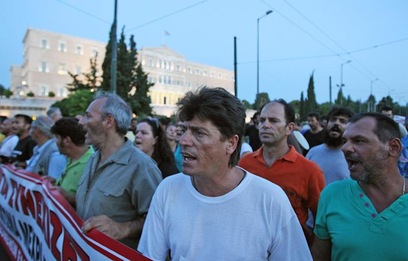 Protesting steelworkers chant anti-government slogans in front of parliament, on Monday, July 23, 2012. Police forced an end to a strike lasting nearly four months at a steel plant near Athens last week. The action triggered a political spat between the country's new conservative-led government and leftwing opposition parties ahead of a new visit to Athens this week by international debt inspectors. (AP Photo/Thanassis Stavrakis)