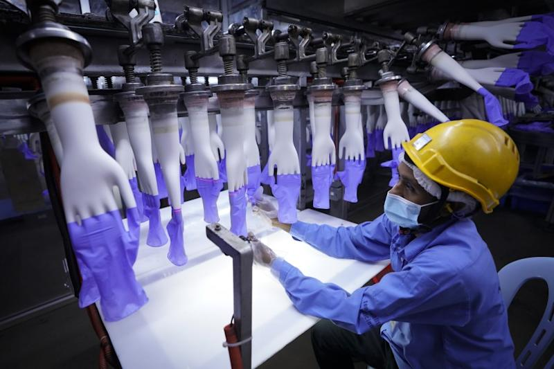 A worker inspects disposable gloves at the Top Glove factory in Shah Alam on the outskirts of Kuala Lumpur, Malaysia, Wednesday, Aug. 26, 2020. Top Glove, a Malaysian-based company, is one of the world's largest rubber glove manufacturer. (AP Photo/Vincent Thian)