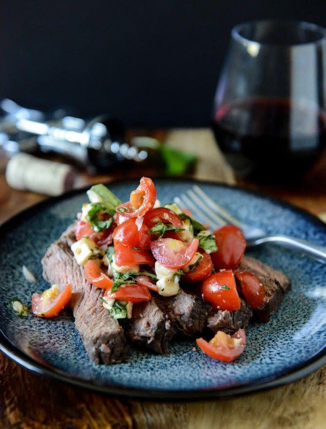 """<strong>Get the <a href=""""http://www.howsweeteats.com/2013/04/red-wine-marinated-flank-steak-with-cherry-tomato-caprese-salsa/"""" rel=""""nofollow noopener"""" target=""""_blank"""" data-ylk=""""slk:Red Wine Marinated Flank Steak with Cherry Tomato Caprese Salsa recipe"""" class=""""link rapid-noclick-resp"""">Red Wine Marinated Flank Steak with Cherry Tomato Caprese Salsa recipe</a> from How Sweet It Is</strong>"""